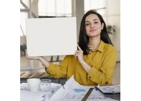 女商人在工作时拿着一张空白卡片_12140643