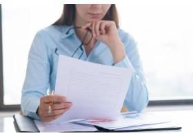 女子手持和阅读文件的特写_3295441