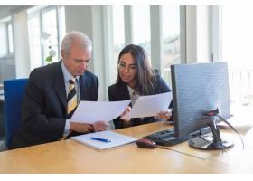 女性专业人员在工作场所向客户解释文件细节_12615862