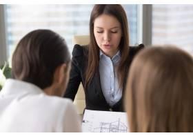 女性严肃的房地产经纪人与客户讨论建房计划_3938463