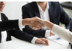 女性在小组会议上握手进行伙伴关系交易特_3952596