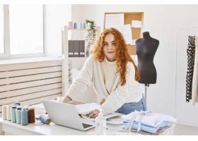 女时装设计师用笔记本电脑在工作室工作的前_12364434