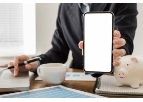 商务人士在办公室拿着空白智能手机的前视图_11383078