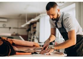 在一家工廠工作的男性設計師和皮革裁縫_12804145