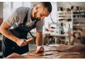 在一家工廠工作的男性設計師和皮革裁縫_12804147
