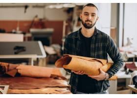 在一家工廠工作的男性設計師和皮革裁縫_12804151