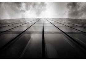 在多云的天空下有玻璃窗的墙壁上的摩天大楼_8943864