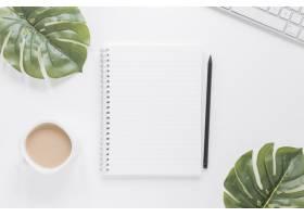 咖啡杯旁的笔记本和绿叶桌子上的键盘_5421238