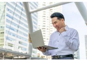 商业报道亚洲男士在商业区使用笔记本电脑都_11872210