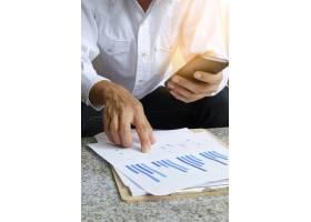 商人手持手机在平板电脑上分析财务图表_1151954