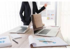 商务人士在会议上使用笔记本电脑和财务图表_1010134