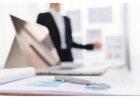 商务人士在会议上使用笔记本电脑和财务图表_1010144