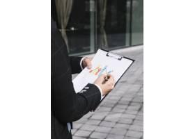 商务人士在剪贴板上手绘递增箭头的特写_3648818