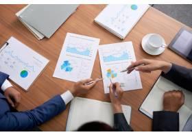 三个面目全非的商人坐在会议上看图表的上图_5577430