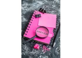 上图为粉红色记事本带笔放大镜和灰色背景_13291715