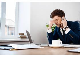 不高兴的年轻商人在电话里说话办公室背景_7855194