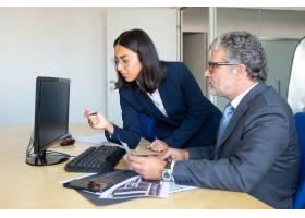 專心致志的男性業務負責人和女性助理看著電_12615871