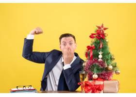 前景令人惊叹的男子坐在圣诞树附近的桌子上_13361367