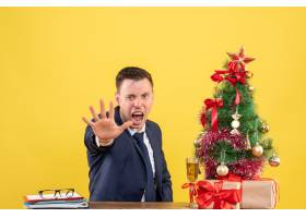 前景愤怒的男子停止手坐在圣诞树附近的桌子_13361465