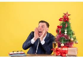 前景愤怒的男子坐在圣诞树附近的桌子旁大声_13361441