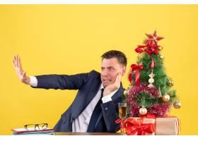 前景焦躁不安的男子试图阻止坐在圣诞树旁的_13361324