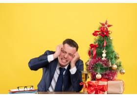 前视一名怒气冲冲的男子坐在圣诞树旁的桌子_13361396