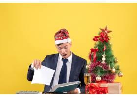 前视商务人员坐在圣诞树附近的桌子旁查看文_13361550
