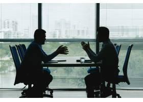 两个人的轮廓映衬着紧闭的办公室窗户面对_5699234