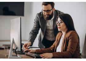 兩個在辦公室一起工作的計算機業務合作伙伴_11601351