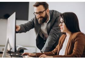 兩個在辦公室一起工作的計算機業務合作伙伴_11601353
