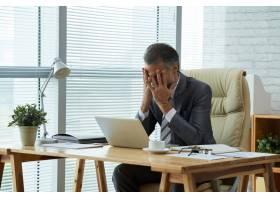 中等镜头一位商人坐在办公桌前双手捂住_5699186