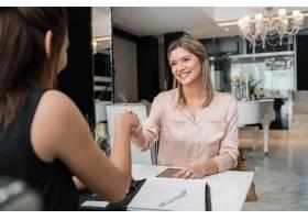 两位年轻女商人在酒店大堂见面握手的肖像_10104153