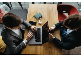 两名男子在咖啡馆开会时用笔记本电脑工作_7621190