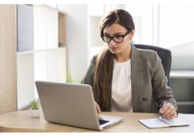 办公室里用笔记本电脑工作的女商人的前视图_10337414