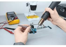 修理损坏的智能手机时维修人员使用镊子和_10897869