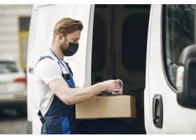 卡车旁边的人穿着送货制服的人戴医用口_13273830