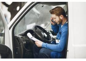 卡车里的人穿着送货制服的人拿着剪贴板_13273855