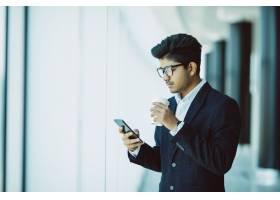 印度商人在办公室打电话喝咖啡_9076263