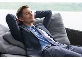 双手放在脑后的微笑男子在沙发上打瞌睡_999489