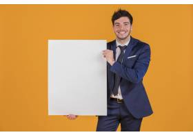 一位年轻商人在橙色背景下举着白色空白标语_4502538