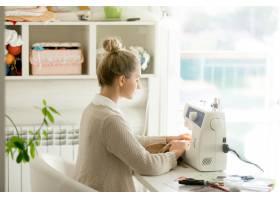 一位年轻漂亮女子在缝纫机前的侧影_1281042