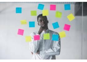 一位年轻的生意人站在不干胶玻璃墙前在他_8989587