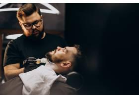 一位英俊的男子在理发店剪胡子_7435501