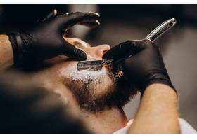 一位英俊的男子在理发店剪胡子_7435504