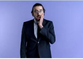 一位身穿黑色西装戴着眼镜的商人站在蓝色_12328528