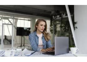 一位金发女商人在笔记本电脑前工作_12140678