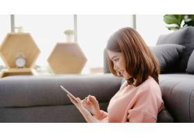一名亚洲妇女躺在客厅的家里沙发上使用平板_4691899