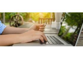一名女子手持信用卡用笔记本电脑输入安全_1382938