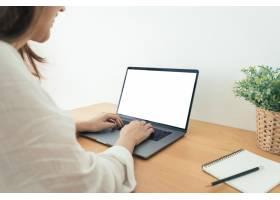 一名年轻的亚洲女性在模拟白屏笔记本电脑上_3517442