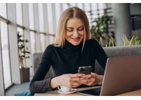 一名年轻的女商人在咖啡馆里用笔记本电脑工_13377035